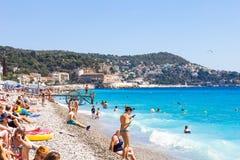 Os turistas apreciam o bom tempo na praia em agradável, França Imagens de Stock Royalty Free