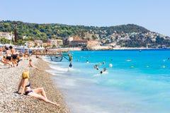 Os turistas apreciam o bom tempo na praia em agradável, França Imagem de Stock