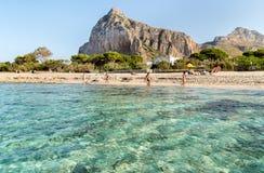 Os turistas apreciam o mar Mediterrâneo na praia famosa de San Vito Lo Capo Foto de Stock
