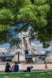 Os turistas apreciam o sol e a máscara pela ponte da torre em Londres Foto de Stock