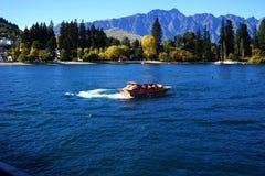 Os turistas apreciam um passeio de alta velocidade do barco do jato no rio de Shotover em Queenstown, Nova Zelândia Fotografia de Stock Royalty Free