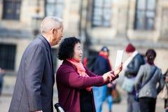 Os turistas asiáticos que usam seus telefones celulares para tomar imagens na represa esquadram em Amsterdão foto de stock royalty free