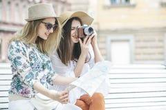 Os turistas bonitos das meninas estão procurando um endereço no mapa que senta-se no banco fotografia de stock