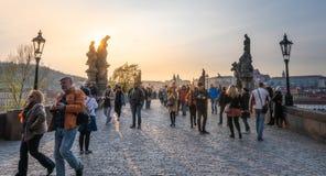 Os turistas cruzam Charles Bridge famoso no capital em uma noite brilhante do por do sol imagens de stock royalty free