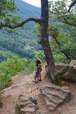 Os turistas da mamã e do filho estão olhando da montanha alta para ver abaixo fotografia de stock
