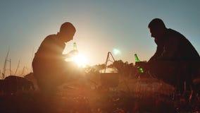 Os turistas da silhueta dois estão sentando o estilo de vida pela fogueira da cerveja fazem o selfie em um partido do smartphone  vídeos de arquivo