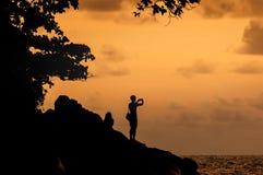 Os turistas da silhueta tomam a imagem na praia no tempo do por do sol Foto de Stock Royalty Free