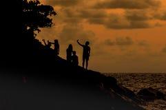 Os turistas da silhueta tomam a imagem na praia no tempo do por do sol Foto de Stock