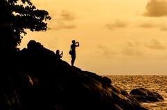 Os turistas da silhueta tomam a imagem na praia no tempo do por do sol Fotos de Stock Royalty Free