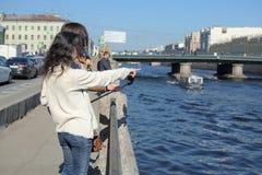 Os turistas das jovens senhoras em Saint Peteresburg R?ssia apreciam o ver?o em um dia ensolarado e cumprimentam barcos sightseei imagens de stock