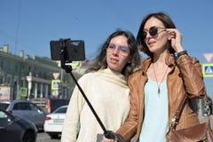 Os turistas das jovens senhoras fazem selfies em uma ponte em St Petersburg, R?ssia, e t?m o divertimento na frente da c?mera foto de stock royalty free