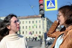 Os turistas das jovens senhoras têm uma parada em uma ponte em St Petersburg, Rússia e discutem sightseeing mais adicional imagens de stock royalty free