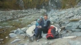 Os turistas descansam após uma caminhada cursos da família Ambiente dos povos por montanhas, rios, córregos Os pais e as crianças filme