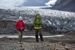 Os turistas do homem e da mulher estão no fundo de uma geleira em Islândia fotografia de stock royalty free