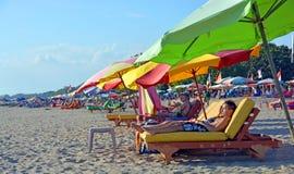 Os turistas dormitam em cadeiras do Recliner na praia de Legian, Bali Foto de Stock