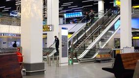 Os turistas e o pessoal do aeroporto descem a escada rolante do terminal de aeroporto vídeos de arquivo
