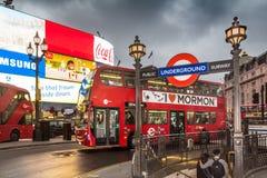 Os turistas entram no metro subterrâneo de Londres pelo circo néon-iluminado de Picadilly no crepúsculo imagens de stock