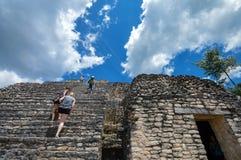 Os turistas escalam as escadas da pirâmide de Caana no local arqueológico da civilização do Maya, Belize ocidental de Caracol fotos de stock royalty free