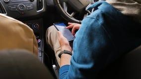 Os turistas escolhem o sentido no mapa no telefone O homem está procurando um destino, sentando-se no carro E vídeos de arquivo