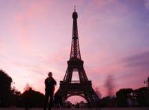 Os turistas espectrais cercam a torre Eiffel na noite Imagem de Stock