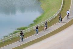 Os turistas estão apreciando a ciclagem na pista da bicicleta imagens de stock