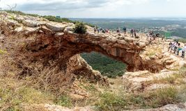 Os turistas estão e olham a caverna de Keshet - arco natural antigo da pedra calcária que mede as sobras de uma caverna rasa com  foto de stock royalty free