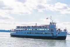 Os turistas estão embarcando o barco dos cruzeiros da estátua fotos de stock