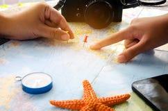 Os turistas estão planejando uma viagem em um mapa e marcam um lugar do intere fotografia de stock