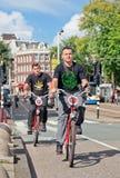 Os turistas exploram o centro em bicicletas alugado de Mac Bike, Amsterdão de Amsterdão, Países Baixos Fotografia de Stock