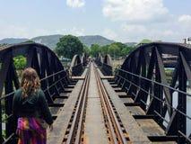 Os turistas fêmeas novos andam ao longo da ponte do rio Kwai imagem de stock royalty free