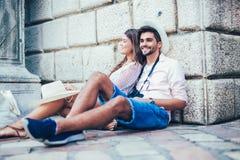 Os turistas felizes descansam na rua ao explorar a cidade foto de stock