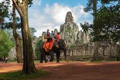 Os turistas montam elefantes após o templo de Bayon em Camboja imagem de stock