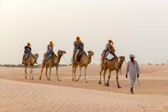 Os turistas montam nos camelos guiados por um homem local, no deserto de Sahara, Tunísia, África fotografia de stock