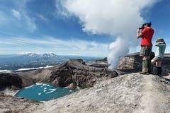 Os turistas na cratera do vulcão ativo de Gorely tomam uma imagem Rússia, Kamchatka Fotos de Stock Royalty Free