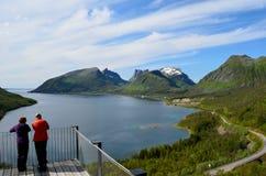 Os turistas na vigia apontam, senja com céu azul e paisagem do fiorde Foto de Stock Royalty Free