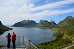 Os turistas na vigia apontam, senja com céu azul e paisagem do fiorde Fotos de Stock