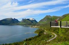 Os turistas na vigia apontam, senja com céu azul e paisagem do fiorde Fotografia de Stock Royalty Free