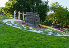 Os turistas no parque que senta-se sobre a inclinação contemplam uma escultura no meio do canteiro de flores feito no formulário fotografia de stock royalty free