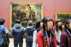 Os turistas olham as pinturas de Eugene Delacroix no museu do Louvre (Musee du Louvre) fotos de stock