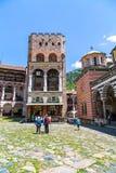 Os turistas perto do ícone compram no monastério famoso de Rila, Bulgária Fotografia de Stock