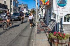 Os turistas que andam e que bicycling abaixo da rua principal que olha em lojas com carros estacionaram ao longo da rua e dos cãe fotografia de stock