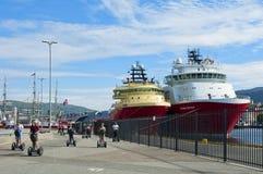 Os turistas que montam segways e navios amarraram no porto de Bergen imagens de stock royalty free