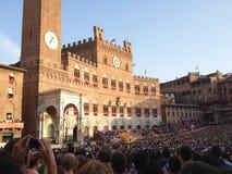 Os turistas que olham o traje tradicional colorido e extravagante desfilam na corrida de cavalos, di Siena de Palio, realizada no imagens de stock royalty free
