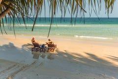 Os turistas relaxam na luz do sol da noite em uma praia tropical Fotografia de Stock
