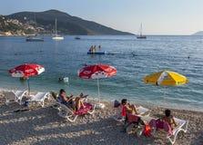 Os turistas relaxam na praia em Kalkan em Turquia no final da tarde Imagens de Stock Royalty Free