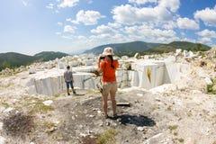 Os turistas são fotografados na pedreira de mármore abandonada velha Fotos de Stock
