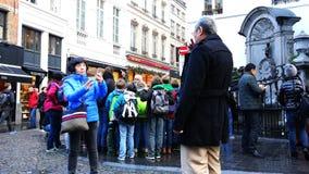 Os turistas são fotografados perto da escultura do ` de Manneken Pis do ` vídeos de arquivo