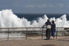 Os turistas superiores dos povos observam ondas esmagar em um cais Fotografia de Stock Royalty Free