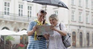 Os turistas superiores felizes estão do centro e apreciam o tempo chuvoso em Lviv filme
