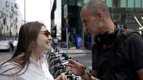 Os turistas, um homem e uma mulher, comunicam perto do planeamento alugado da bicicleta uma excursão da cidade vídeos de arquivo